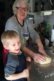 Karin Furst baking with her great grandson