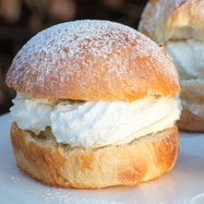 A Swedish semla bun filled with almond paste and whipped cream