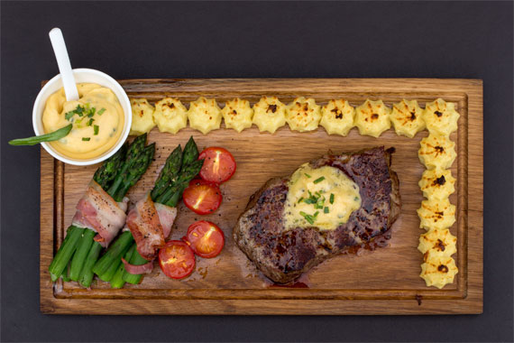 Swedish plankstek served with duchess potatoes, asparagus wrapped in bacon and bearnaise sauce