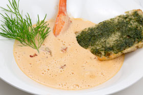 A bowl of lobster soup garnished with dill toast