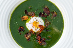 Nettle soup garnished with crispy pancetta and a poached egg