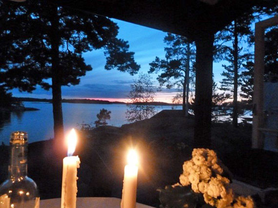 A candle lit table set near a lakeside