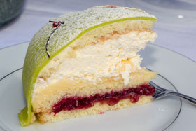 A slice of princess cake showing a layer of raspberry jam